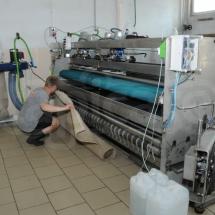 Wkładanie dywanu do maszyny trzepiącej